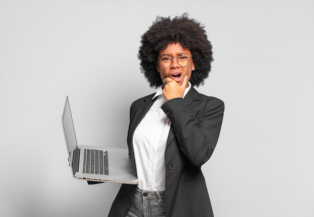 Jeune femme d'affaires afro avec la bouche et les yeux grands ouverts et la main sur le menton, se sentant désagréablement choquée, disant quoi ou wow. concept d'entreprise