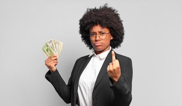 Jeune femme d'affaires afro se sentant en colère, ennuyée, rebelle et agressive, retournant le doigt du milieu, ripostant