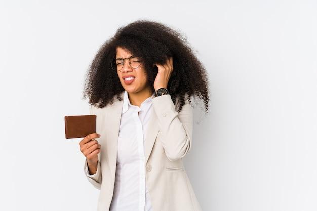 Jeune femme d'affaires afro tenant une voiture de crédit isolée jeune femme d'affaires afro tenant une voiture de crédit couvrant les oreilles avec les mains.