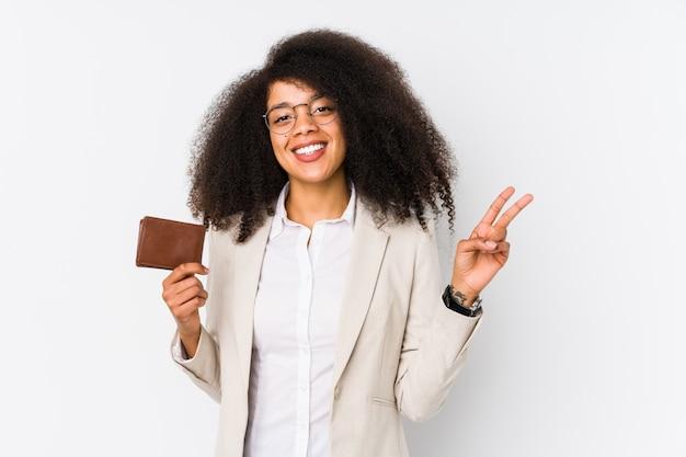Jeune femme d'affaires afro tenant une voiture de crédit isolée jeune femme d'affaires afro tenant une voiture de crédit joyeuse et insouciante montrant un symbole de paix avec les doigts.