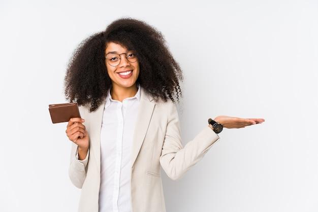 Jeune femme d'affaires afro tenant une voiture de crédit isolée jeune femme d'affaires afro tenant une voiture de crédit montrant un espace de copie sur une paume et tenant une autre main sur la taille.