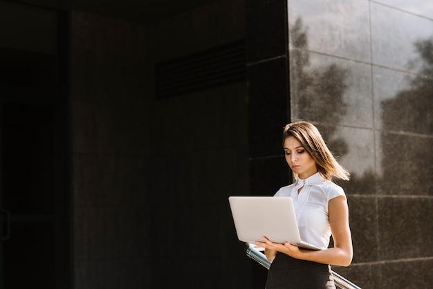 Jeune femme d'affaires à l'aide d'un ordinateur portable à l'extérieur du bâtiment