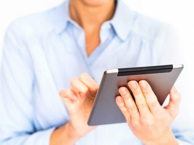 Jeune femme d'affaires à l'aide de sa tablette