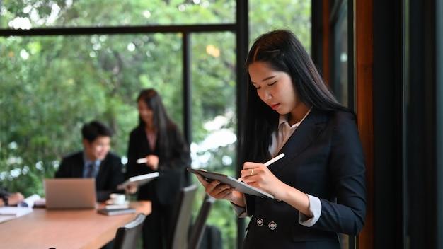 Jeune femme d'affaires à l'aide de stylet rabotage écrit son projet sur tablette dans la salle de réunion.