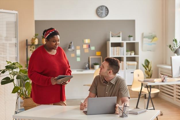 Jeune femme d'affaires à l'aide de tablet pc et de parler à son collègue pendant qu'il utilise un ordinateur portable, ils travaillent en équipe