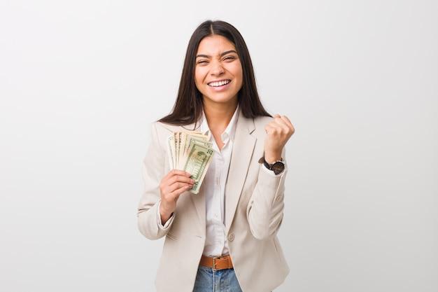 Jeune femme d'affaires arabe détenant des dollars acclamant insouciante et excitée. concept de victoire.