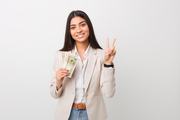 Jeune femme d'affaires arabe détenant des dollars montrant le numéro deux avec les doigts.