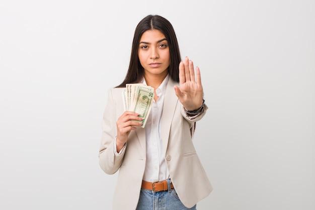 Jeune femme d'affaires arabe tenant des dollars debout avec la main tendue montrant le panneau d'arrêt