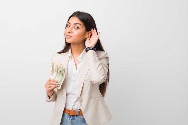 Jeune femme d'affaires arabe tenant des dollars en essayant d'écouter un commérage.
