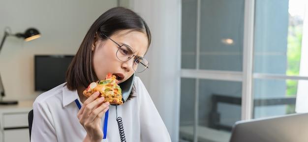 Jeune femme d'affaires asiatique ayant une collation de pizza tout en parlant au téléphone avec les clients en raison du travail tardif.