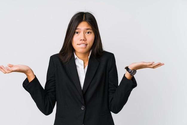 Jeune femme d'affaires asiatique confuse et douteuse en haussant les épaules pour tenir un espace de copie.