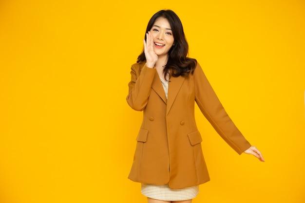 Jeune femme d'affaires asiatique en costume de discours et annoncer isolé sur fond jaune
