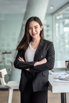 Jeune femme d'affaires asiatique debout au bureau.
