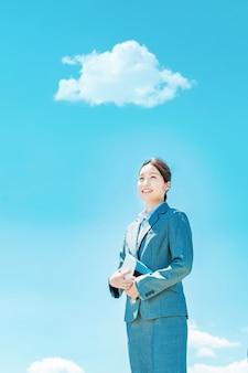 Jeune femme d'affaires asiatique debout contre le ciel bleu