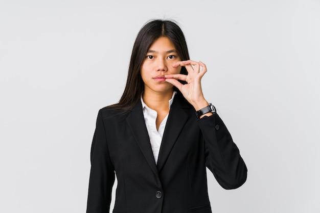 Jeune femme d'affaires asiatique avec les doigts sur les lèvres gardant un secret.