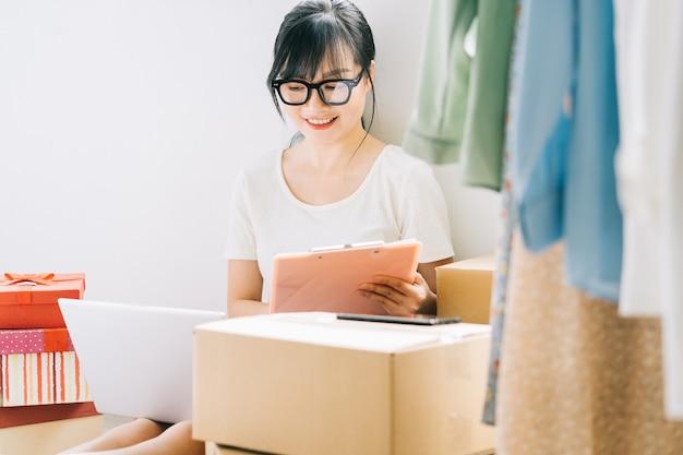 Jeune femme d'affaires asiatique est assise sur le sol pour vérifier ses commandes sur les sites de commerce électronique