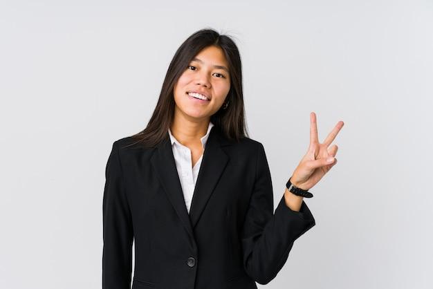 Jeune femme d'affaires asiatique joyeuse et insouciante montrant un symbole de paix avec les doigts.