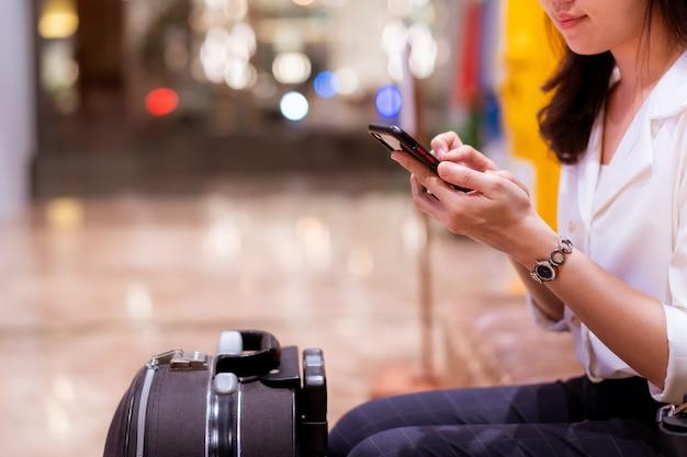 Jeune femme d'affaires asiatique marchant et regardant le smartphone à l'hôtel, femme en affaires décontractées portant une valise - bagages dans le hall de l'hôtel.