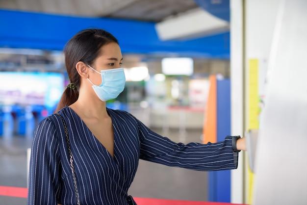Jeune femme d'affaires asiatique avec masque achat de billet à la station de skytrain