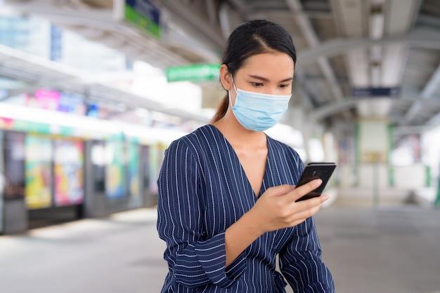 Jeune femme d'affaires asiatique avec masque à l'aide de téléphone tout en étant assis à la station de skytrain