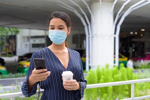 Jeune femme d'affaires asiatique avec masque à l'aide de téléphone tout en prenant un café sur le pouce comme la nouvelle norme pendant le covid-19