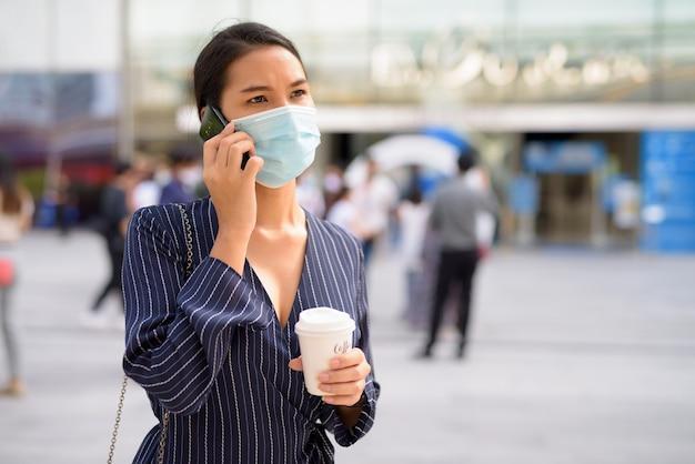 Jeune femme d'affaires asiatique avec masque parlant au téléphone tout en prenant un café sur le pouce comme la nouvelle normale à l'extérieur