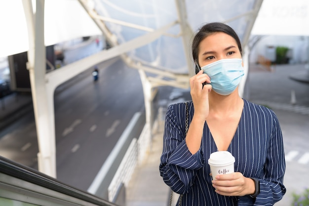 Jeune femme d'affaires asiatique avec masque parlant au téléphone tout en prenant un café sur le pouce comme la nouvelle norme dans la ville