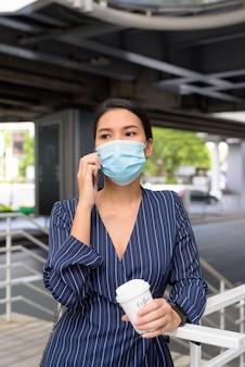 Jeune femme d'affaires asiatique avec masque parlant au téléphone tout en prenant un café sur le pouce comme la nouvelle norme pendant le covid-19
