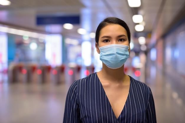 Jeune femme d'affaires asiatique avec masque pour se protéger de l'épidémie de virus corona à la station de métro