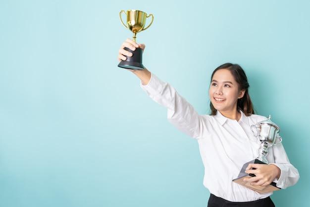 Jeune femme d'affaires asiatique montrant un trophée d'or