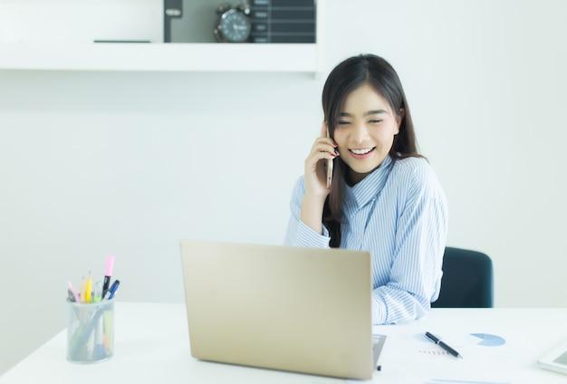 Jeune femme d'affaires asiatique parlant au téléphone mobile et souriant sur son lieu de travail
