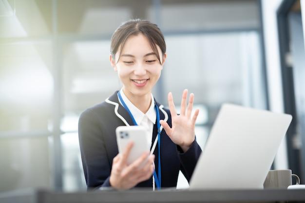 Jeune femme d'affaires asiatique parlant à l'écran de son smartphone