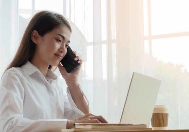 Jeune femme d'affaires asiatique parlant de téléphone intelligent et travaillant avec labtop