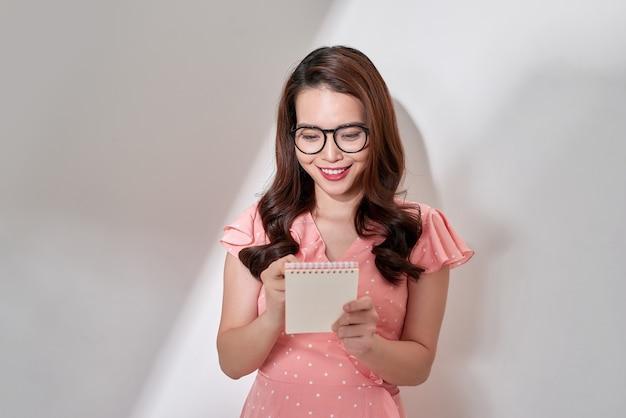 Jeune femme d'affaires asiatique avec presse-papiers se faire une idée isolée sur fond blanc