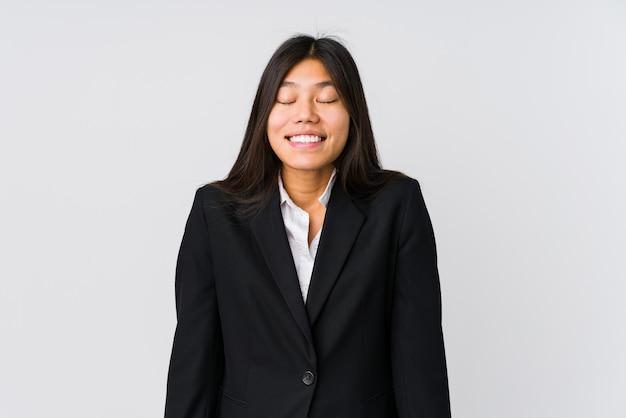 Jeune femme d'affaires asiatique rit et ferme les yeux, se sent détendue et heureuse.