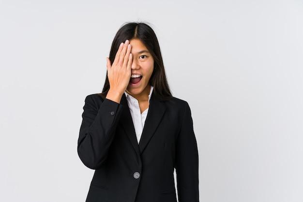 Jeune femme d'affaires asiatique s'amuser couvrant la moitié du visage avec la paume.