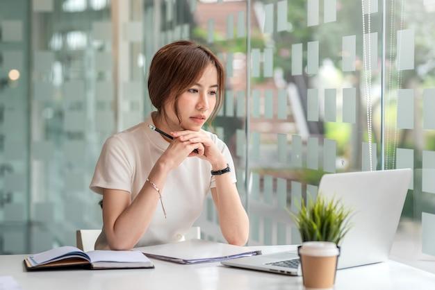Jeune femme d'affaires asiatique se concentrant à l'aide d'un ordinateur portable au bureau.