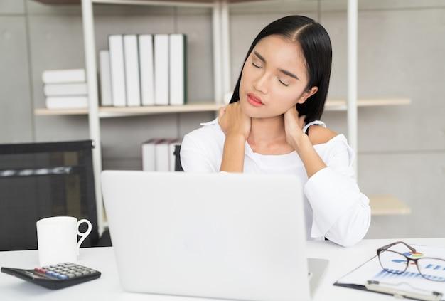 Jeune femme d'affaires asiatique souffrant de douleurs au cou