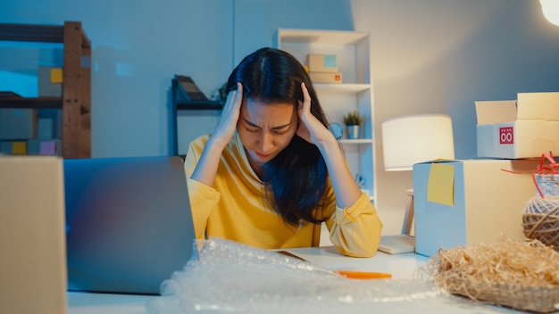 Jeune femme d'affaires asiatique a souligné et contrarié par une mauvaise vente au bureau à domicile pendant la nuit