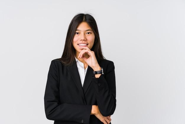 Jeune femme d'affaires asiatique souriant heureux et confiant, touchant le menton avec la main.