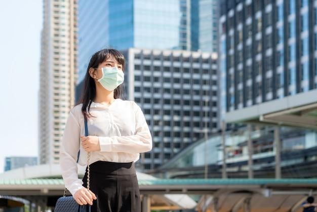 Jeune femme d'affaires asiatique stressée en chemise blanche va travailler dans la ville de la pollution, elle porte un masque de protection contre la poussière et covid-19 avec un immeuble de bureaux à bangkok, en thaïlande.
