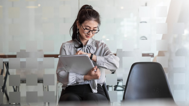 Jeune femme d'affaires asiatique tenant un portefeuille regarde l'horloge attend un entretien d'embauche au bureau.