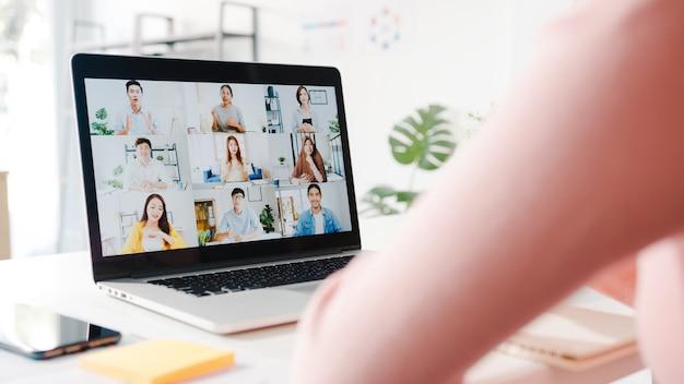 Une jeune femme d'affaires asiatique utilisant un ordinateur portable parle à un collègue du plan lors d'une réunion par appel vidéo pendant qu'elle travaille à domicile dans le salon.
