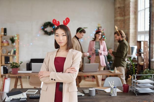 Jeune femme d'affaires asiatique en vêtements décontractés intelligents et chapeaux de noël debout au bureau contre un groupe de collègues ayant une discussion