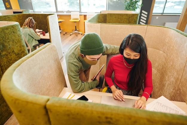 Jeune femme d'affaires asiatique en vêtements de sport intelligents et masque de protection agitant la main tout en regardant un couple heureux sur un écran d'ordinateur portable