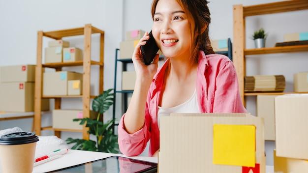 Jeune femme d'affaires d'asie utilisant un appel téléphonique mobile recevant un bon de commande et vérifiez le produit en stock, travaillez au bureau à domicile propriétaire de petite entreprise, livraison de marché en ligne, concept indépendant de style de vie.