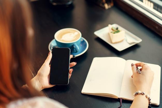 Jeune femme d'affaires assis à la table dans un café et prendre des notes