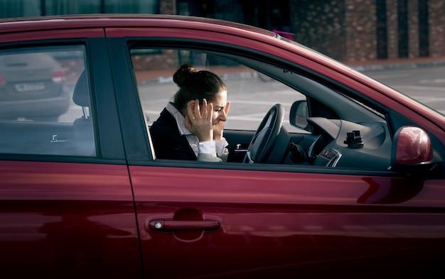 Jeune femme d'affaires assise dans la voiture et criant de peur