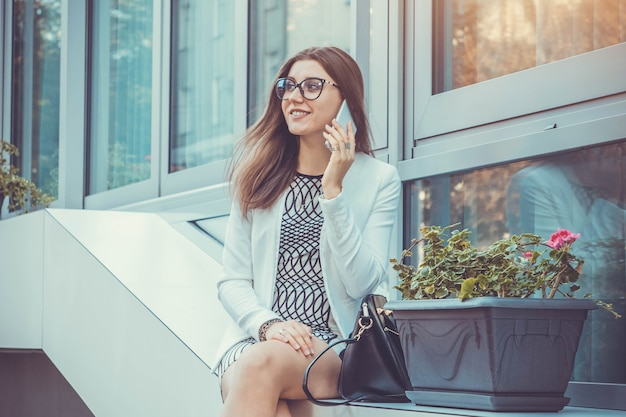 Jeune femme d'affaires assise près du centre d'affaires et parlant au téléphone assise près du centre d'affaires