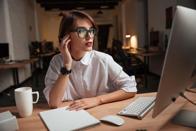 Jeune femme d'affaires attirante sérieuse dans des verres écrivant et utilisant l'ordinateur dans le bureau